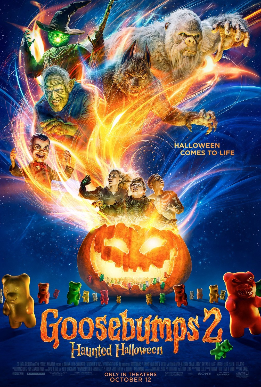 A  large jack-o-lantern has three kids standing in it with what looks like fireworks behind them.  A witch, Frankenstein's monster, a werewolf, and other scary creatures loom behind them.