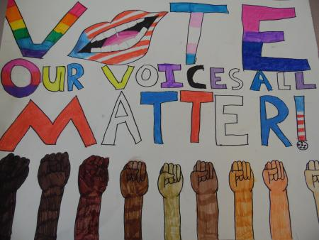 The-text-'Vote-our-voices-all-matter!'-written-in-rainbow-letters-with-a-mouth-as-the-'o'-in-vote.-The-bottom-of-the-design-is-lined-with-drawing-of-fists-of-all-shades-of-skin-tones.-