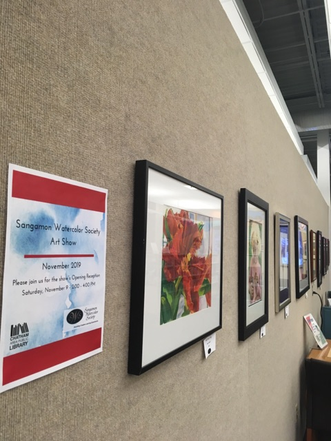 Image of several watercolor paintings on the wall at the Library.