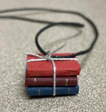 Stack of books turned into a necklace pendant